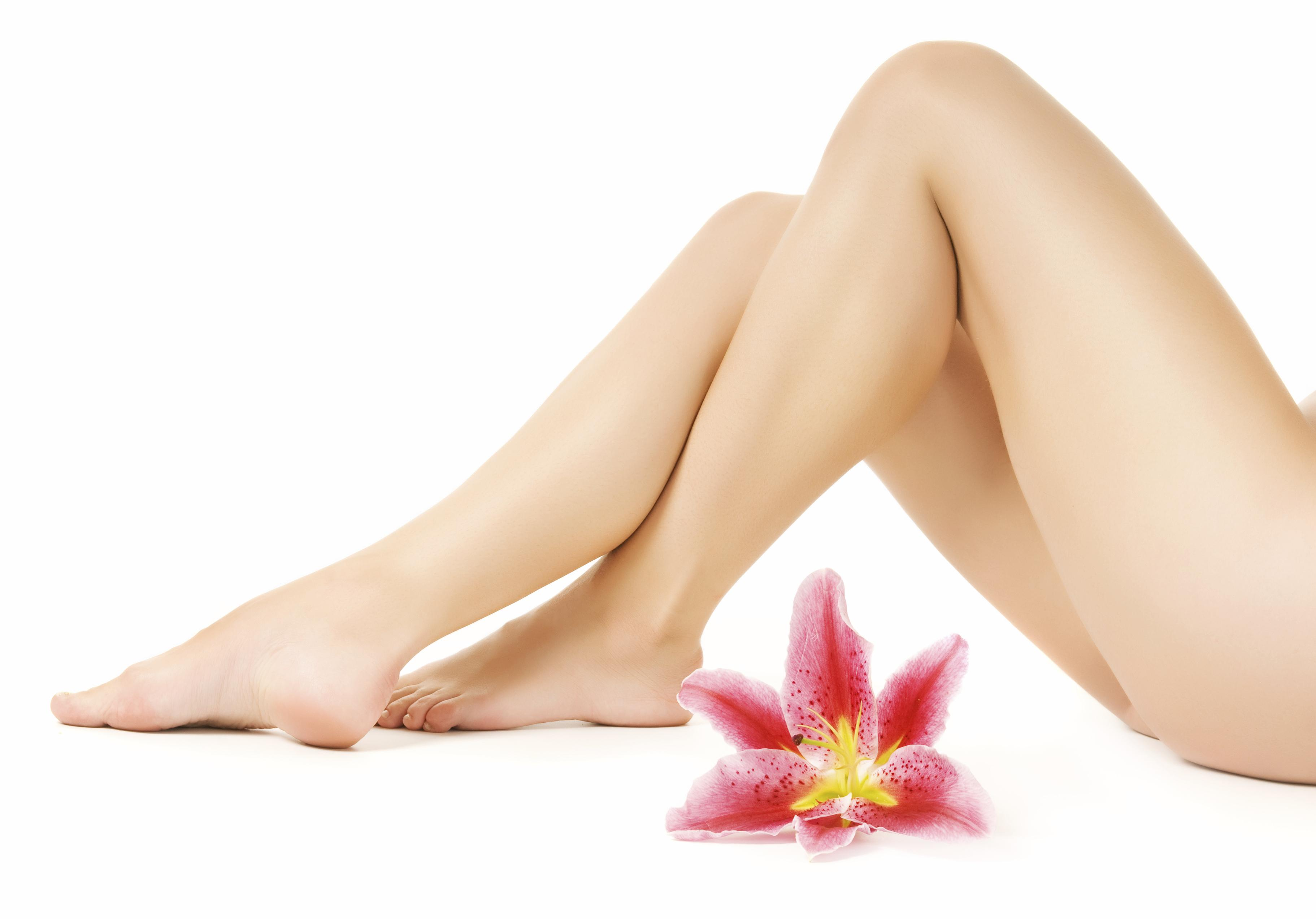 Female legs with pink lily isolated on white background
